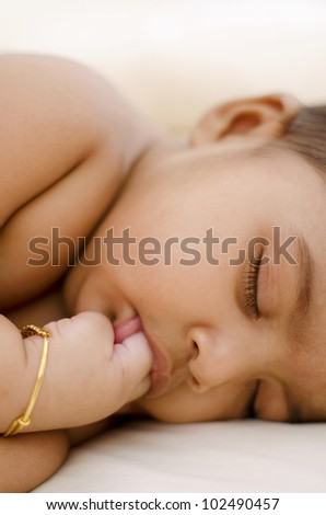 Indian baby girl having sweet dreams, sucking her fingers - stock photo