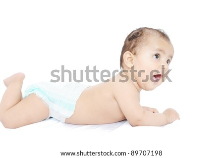 Indian baby laying on bed. - stock photo