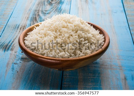 indian basmati rice, pakistani basmati rice, asian basmati rice, cooked basmati rice, cooked white rice, cooked plain rice in wooden bowl over blue wooden background - stock photo