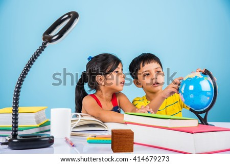 indian boy and girl studying with globe on study table, asian kids studying, indian kids studying geography, kids doing homework or home work, two kids studying on table - stock photo
