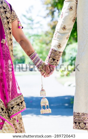 Indian bride and groom holding hands in traditional outfit. - stock photo