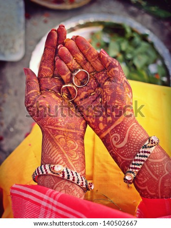 Indian bride doing ring rituals with henna on hands - stock photo
