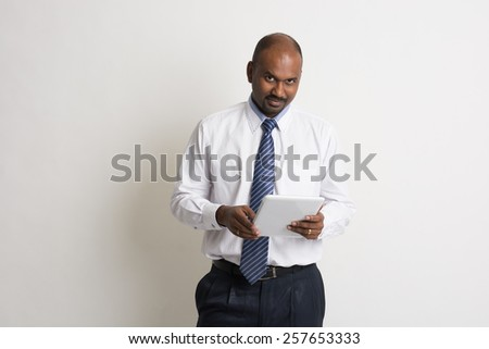 indian business male holding a computer tablet - stock photo