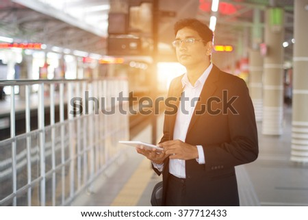 indian business male using tablet computer while waiting for train - stock photo