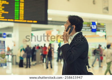 indian business male with a phone at the airport - stock photo
