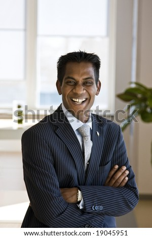 Indian Business Man Laughing with Arms Folded Indoors - stock photo