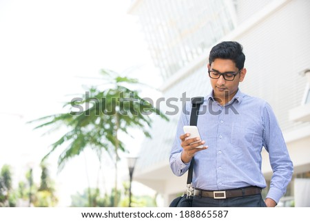 indian business man reading or using smart phone  - stock photo