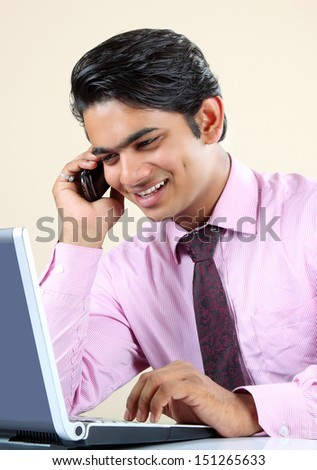 Indian Business man sitting at his desk  with a laptop and using mobile phone. - stock photo