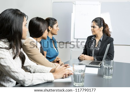 Indian business woman talking with her team during a meeting. - stock photo