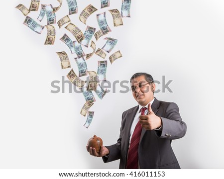 indian businessman catching flying currency in his piggy bank made up or clay, happy asian businessman with piggy bank under falling indian currency notes - stock photo