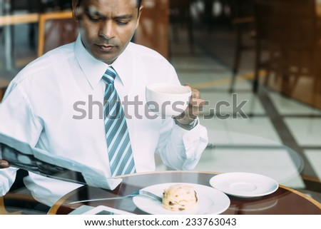 Indian businessman having breakfast and reading newspaper in the cafe - stock photo