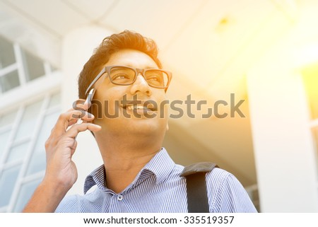 Indian businessman talking on phone in front modern office building. Urban view with sunlight. - stock photo