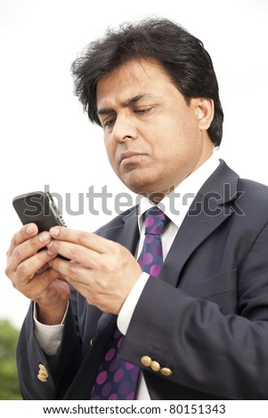 Indian businessman using cell phone - stock photo