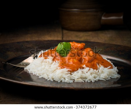 Indian butter chicken on a bed of rice photographed closeup. - stock photo