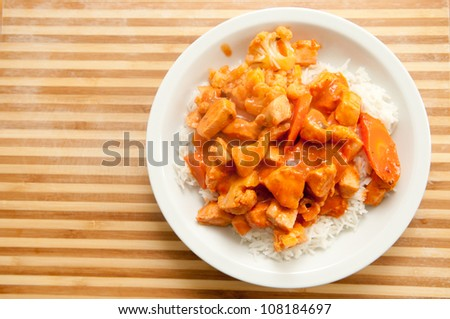 Indian butter chicken with sliced carrot and cauliflower over white rice with a delicious, tasty sauce - stock photo