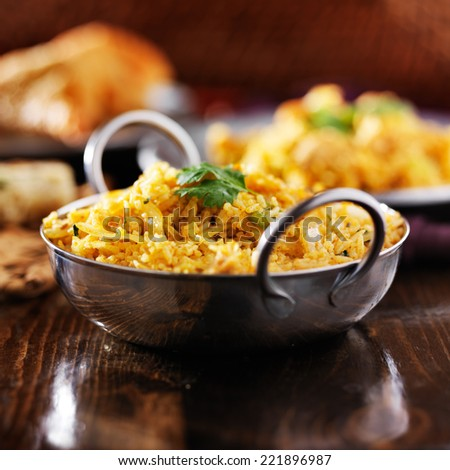 indian chicken biryana in balti dish with naan and samosa in background - stock photo