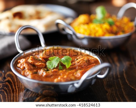 indian chicken curry in balti dish with Biryani in background - stock photo