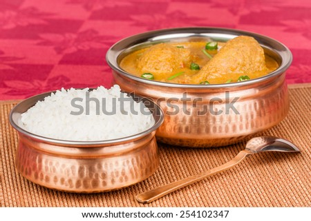 Indian chicken curry served with rice in authentic copper utensils. Green chilli used as garnish. Shallow Depth of field. - stock photo