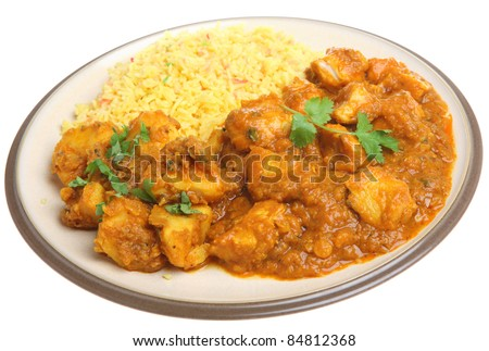 Indian chicken dansak with Bombay aloo potato curry and pilau rice. - stock photo