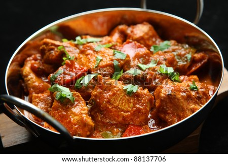 Indian chicken jalfrezi curry. Shallow DoF, focus on central chicken piece. - stock photo