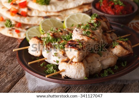 Indian chicken tikka kebabs on skewers close-up on a plate and naan. Horizontal