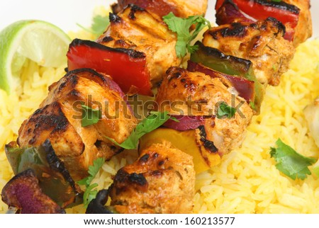 Indian chicken tikka kebabs with red onions and peppers. - stock photo