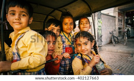 Indian children in yellow uniform going home from school in a Rickshaw. 07, March 2012, Kanpur, India. - stock photo