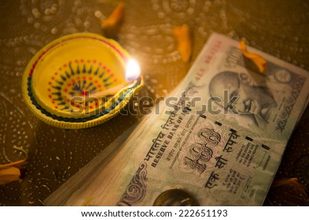 Indian classic lamp and currency notes. Hard cash is worshiped during Diwali puja. - stock photo
