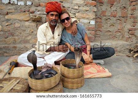 Indian Cobra enchanter and tourist girl - stock photo