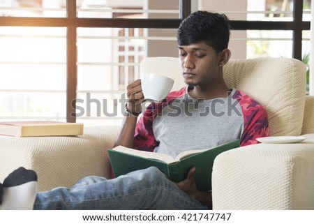 indian college student reading and drinking coffee - stock photo