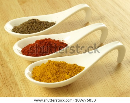 Indian cuisine additions: cumin, turmeric and pepper - stock photo