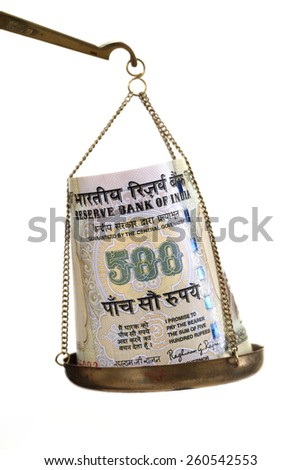 Indian currency note in justice scale - stock photo