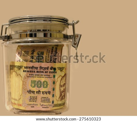 Indian currency notes of rupee 500 in glass jar isolated in off white color backdrop with lot of space for text  - stock photo