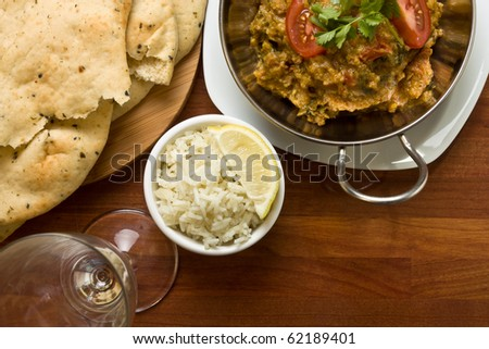 Indian Curry meal of spicy chicken, rice and naan bread. - stock photo