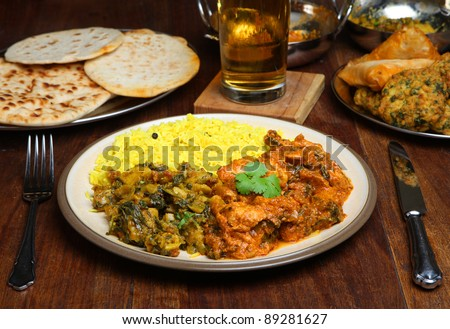 Indian curry meal with naan and lager. - stock photo