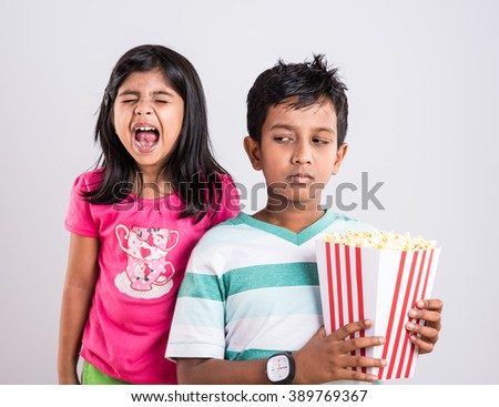 indian cute girl and boy eating popcorn, asian kids and popcorn, Little girl and little boy enjoy eating popcorn and. Leisure time for children, kids eating popcorn, isolated on white - stock photo