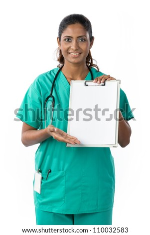 Indian doctor showing clipboard with space for a message. - stock photo