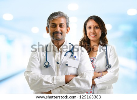 Indian doctors or medical team crossed arms standing, hospital background - stock photo