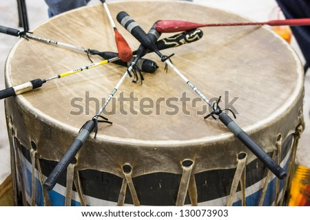 Indian drum and drum sticks placed in  a symbolic manner after the drummers complete their song at a Native American pow-wow. - stock photo