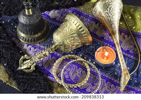 Indian ethnic still life with old ritual bells and candle - stock photo