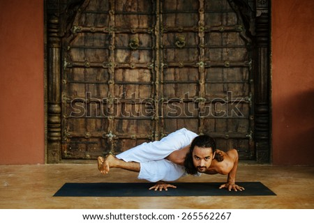 Indian ethnicity young man wit a strong body showing difficult yoga pose (Eight Angle Pose - Astavakrasana) in front of old oriental style door. - stock photo