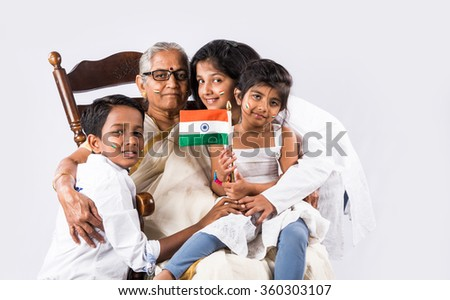 indian family and indian flag, indian family celebrating republican day, independence day and indian flag, old indian woman sitting on chair with grand childrens, 2 small girls with grandmother & flag - stock photo