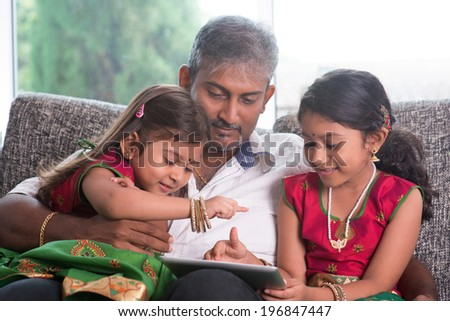 Indian family at home. Asian father and children using digital tablet computer, sitting on sofa, home schooling concept. - stock photo