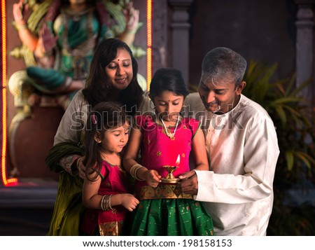 indian family celebrating diwali ,fesitval of lights inside a temple - stock photo
