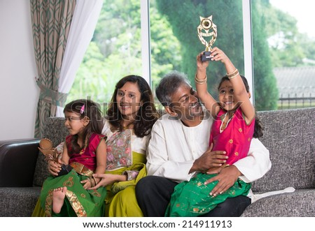 indian family celebrating victory with trophy - stock photo