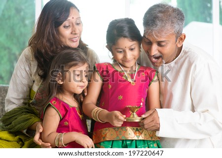 Indian family in traditional sari celebrate diwali or deepavali at home, little girl hands holding oil lamp with father indoors. - stock photo