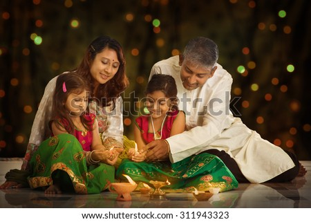 Indian family in traditional sari lighting oil lamp and celebrating Diwali or deepavali, fesitval of lights at home. Little girl hands holding oil lamp indoors. - stock photo