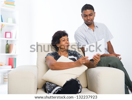 indian family ,mother and son surfing the internet using tablet computer - stock photo