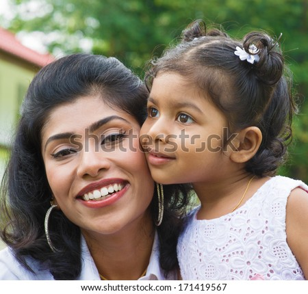 Indian family outdoor. Portrait of loving mother and daughter at garden park. - stock photo