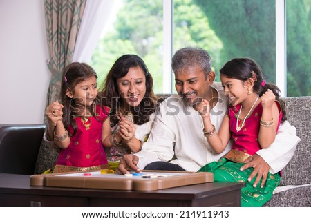 Indian family playing carrom game at home. Parents and children indoor lifestyle. - stock photo